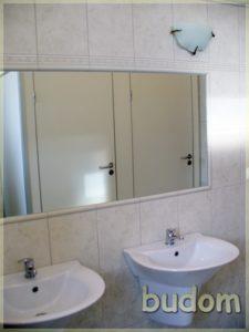 łazienka zkabinami iścianą pokrytą lustrami