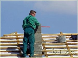 robotnik przy konstrukcji komina